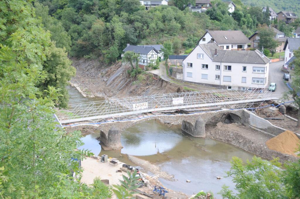 Eine der drei zerstörten Brücken mit Behelfsfußgängerbrücke. Am rechten Bildrand sieht man die weggespülte Straße.